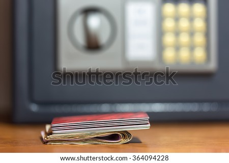Closeup on banknotes and credit cards in front of safety box with electronic lock in hotel. Focus on money and cards - stock photo