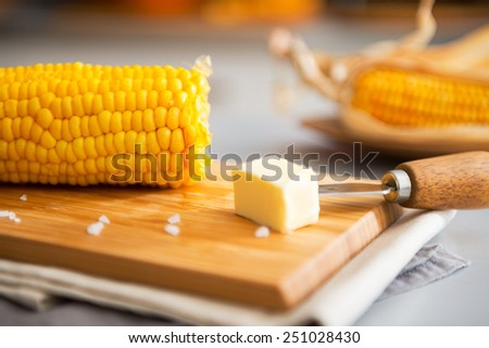 Closeup on boiled corn and butter on cutting board - stock photo