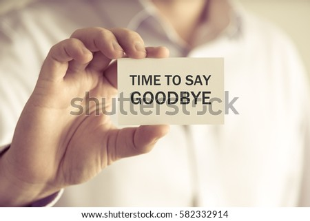 Closeup on businessman holding a card with text TIME TO SAY GOODBYE, business concept image with soft focus background and vintage tone