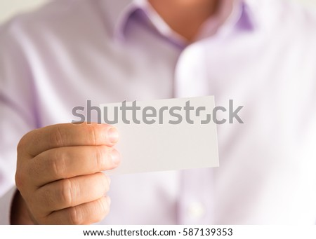 Closeup on businessman holding white empty message card with copy space for text, business concept image with soft focus background