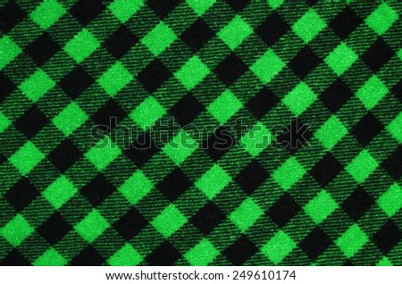 Closeup on checkered tablecloth wool fabric. Green with black gingham square pattern as background.