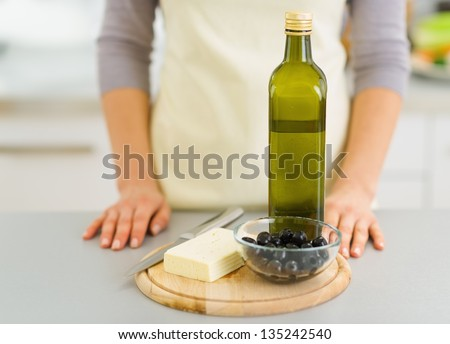 Closeup on cheese, olives and olive oil on cutting board