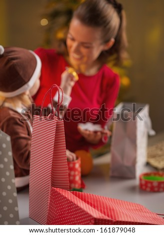 Closeup on christmas shopping bags and mother and baby in background - stock photo