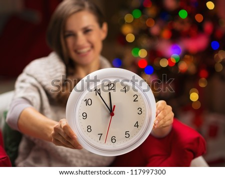 Closeup on clock in hand of happy woman in front of Christmas tree - stock photo