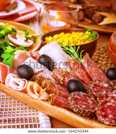 Closeup on cold cuts in centerpiece of table, various of smoked meat, bacon, beef, ham, pepperoni, salami, restaurant menu - stock photo