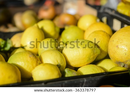 Closeup on colorful lemons on market stall background