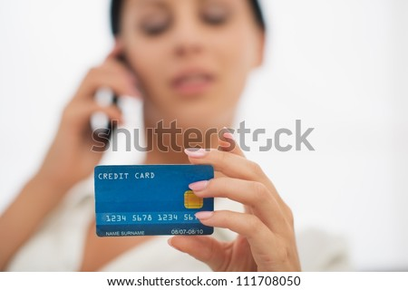 Closeup on credit card in hand of female speaking mobile - stock photo