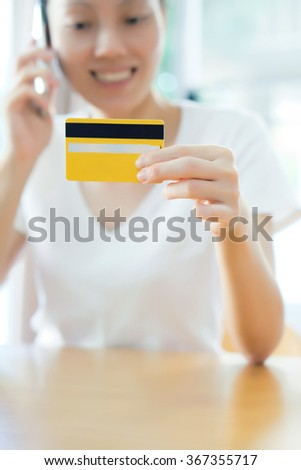 Closeup on credit card in hand of female speaking mobile