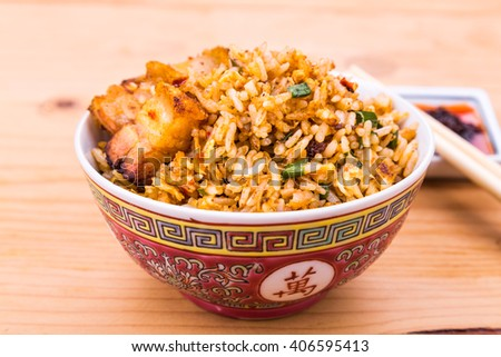 Closeup on delicious Chinese spicy fried rice with roast pork in bowl served on wooden table