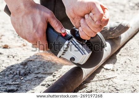Closeup on electric saw and hands. Man working with grinder, close up on tool and sparks fly - stock photo