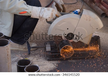 closeup on electric saw and hands of worker with sparks. man working with grinder, close up on tool, sparks fly, real situation picture - stock photo