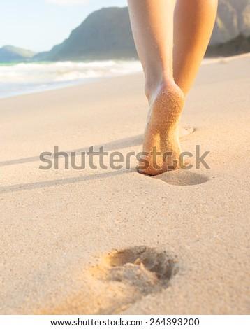 Closeup on feet walking on the beach - stock photo