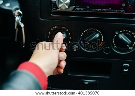 Closeup on female driver turning car air conditioner knob, season changing