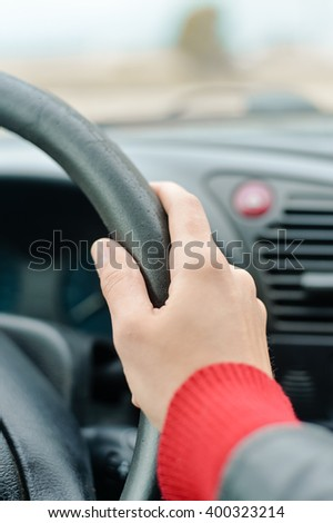 Closeup on female hand driver behind the wheel of a car