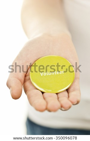 Closeup on female hand holding green volunteer button - stock photo
