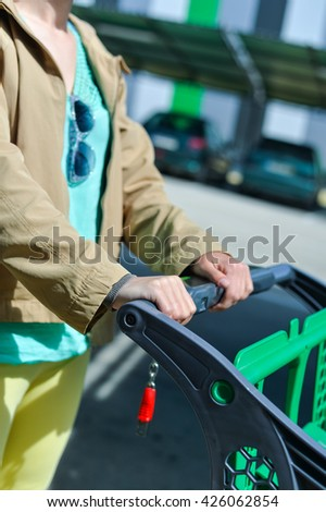 Closeup on female holding shopping push cart. close up picture of hands with car on background - stock photo