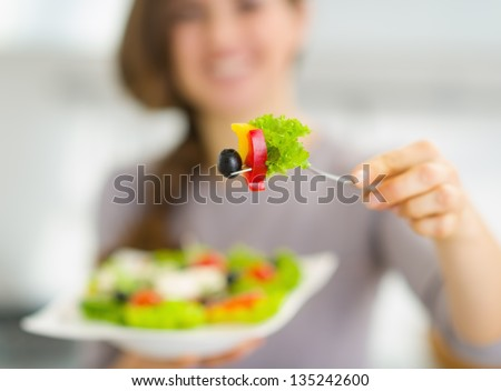 Closeup on fork with salad in hand of young woman - stock photo