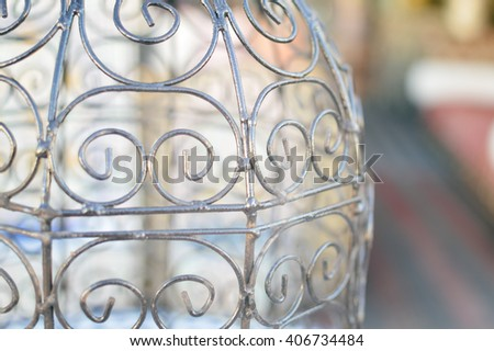 Closeup on fragment of vintage bird cageon on light background - stock photo
