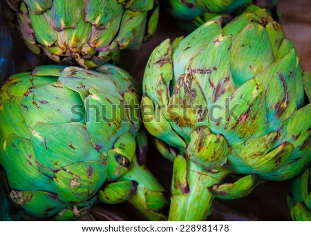 Closeup on Fresh green artichokes in the market, organic vegetables background - stock photo