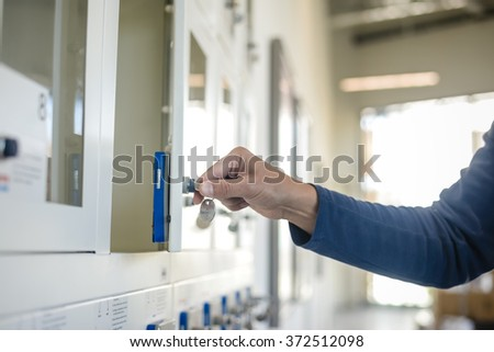 Closeup on hand, door and key in lock on light background. Safekeeping protection concept - stock photo