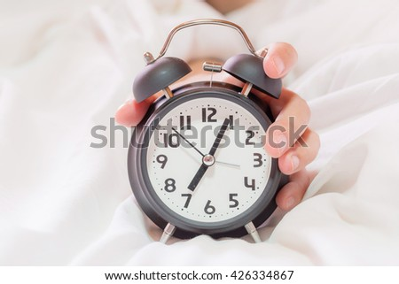 Closeup on hand reaching to turn off alarm clock. beautful fingers