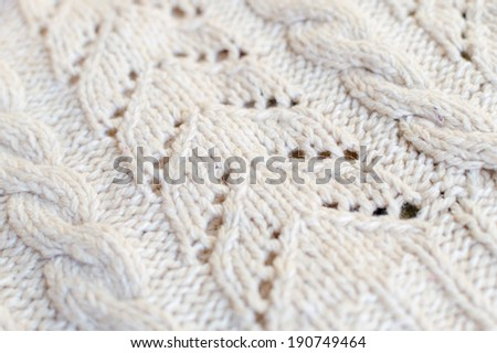 closeup on handmade knitted fabric with white pattern