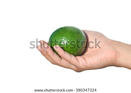 Closeup on hands holding fresh avocado cut in half on light background