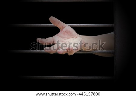 closeup on hands of man sitting in jail. - stock photo