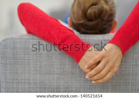 Closeup on hands of young woman laying on divan in living room. rear view - stock photo