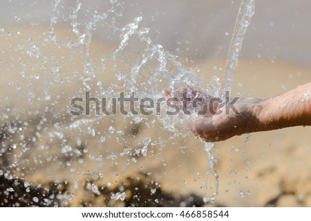 Closeup on hands with water splash, sun light background outdoors