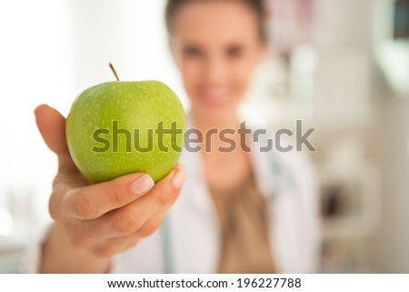 Closeup on happy medical doctor woman giving apple - stock photo
