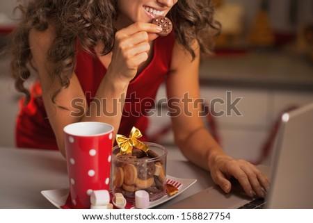 Closeup on happy woman having christmas snacks and usign laptop - stock photo