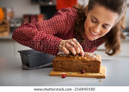 Closeup on happy young housewife decorating freshly baked pumpkin bread with seeds - stock photo