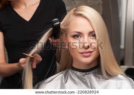 closeup on happy young woman getting new haircut by hairdresser at parlor. hairdresser straightening client's hair in beauty salon - stock photo