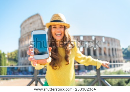 Closeup on happy young woman showing cell phone in front of colosseum in rome, italy - stock photo