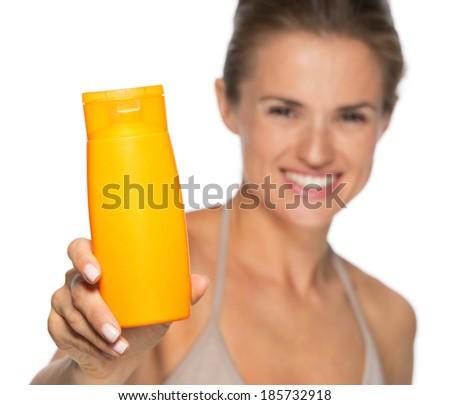 Closeup on happy young woman showing sun screen bottle - stock photo