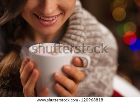 Closeup on hot chocolate with marshmallows in hand of happy girl - stock photo