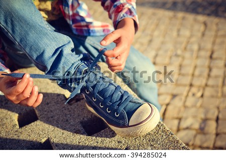 Closeup on kid hands tying laces ready for sport, school fun. Outside sunny background - stock photo