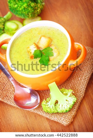 Closeup on little orange bowl with hot tasty cream soup prepared with broccoli, homemade healthy food, vegetarian meal concept - stock photo