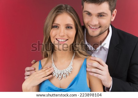 Closeup on man looking at necklace on girl's neck. man standing behind woman wearing jewelry - stock photo
