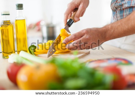 closeup on man's hands cutting vegetables on a work surface in a kitchen - stock photo