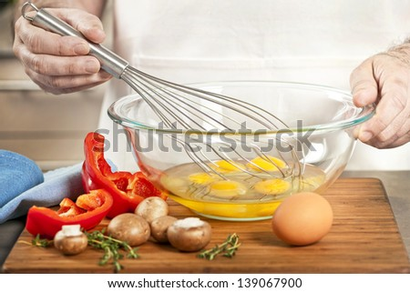 Closeup on man's hands whisking eggs in bowl for cooking omelet with vegetables - stock photo