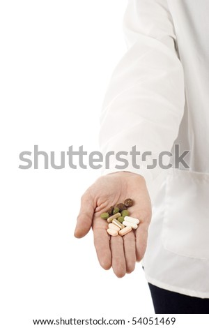Closeup on medical doctor's hand with pills,  isolated over white background