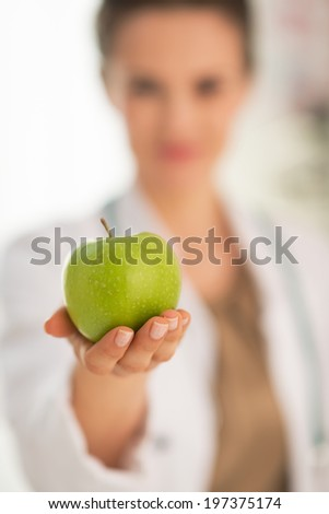 Closeup on medical doctor woman giving apple - stock photo