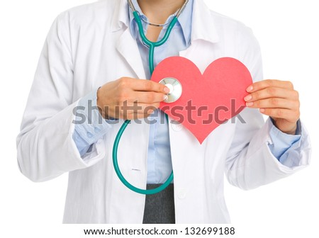 Closeup on medical doctor woman listening paper heart - stock photo