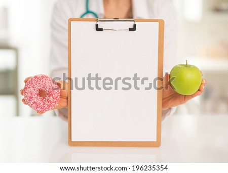 Closeup on medical doctor woman showing blank clipboard apple and donut - stock photo