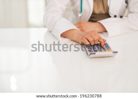 Closeup on medical doctor woman using calculator - stock photo