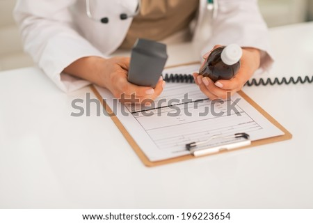 Closeup on medical doctor woman with phone and pills - stock photo