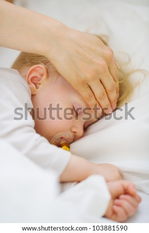 Closeup on mother checking temperature of forehead of baby - stock photo