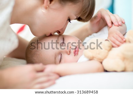 Closeup on mother kissing sleeping baby son - stock photo